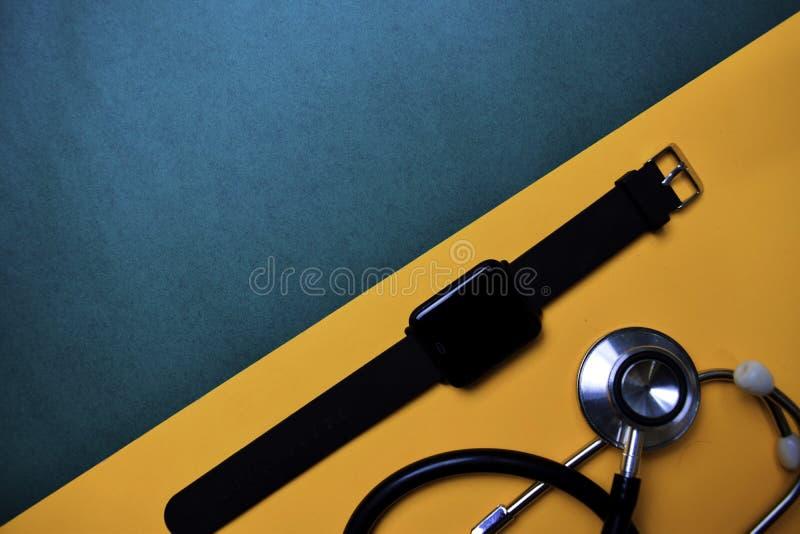 Orologio e stetoscopio astuti sulla tavola di colore di vista superiore e sulla sanità/concetto medico fotografia stock libera da diritti