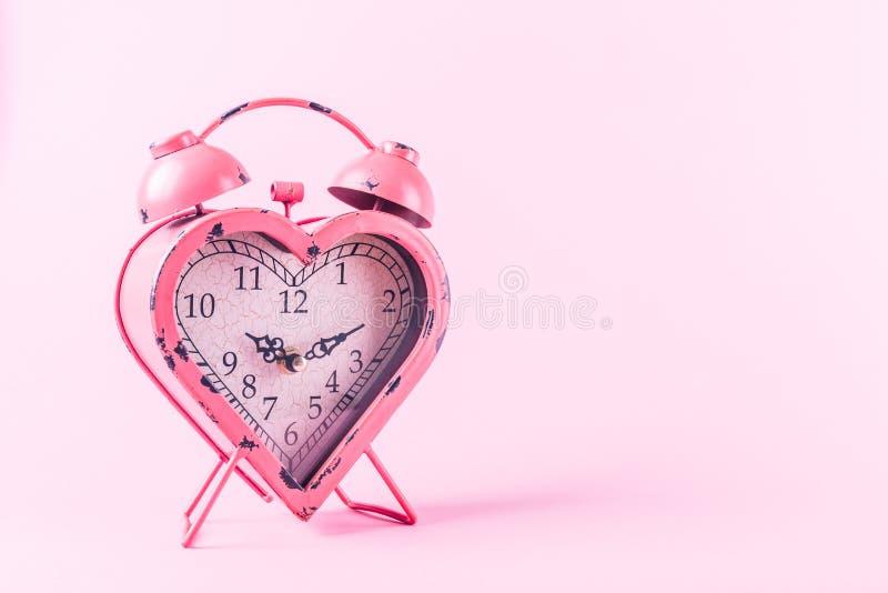 Orologio a forma di del cuore su fondo rosa Giorno ed amore di biglietti di S. Valentino immagini stock libere da diritti