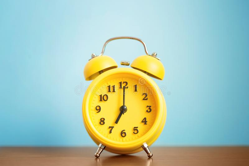Orologio giallo del ` della sveglia sette o di mattina sulla tavola contro la parete blu fotografia stock libera da diritti