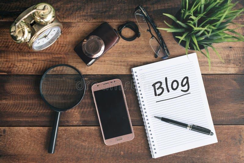 Orologio, macchina fotografica, lente d'ingrandimento, telefono, taccuino con la parola del BLOG su una tavola di legno fotografia stock