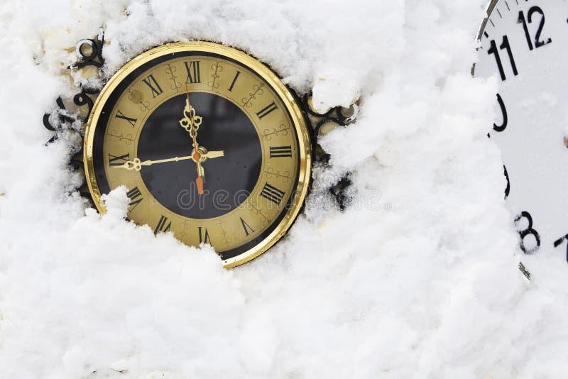 Orologio meccanico che si trova nella neve Il tempo si è arrestato immagine stock libera da diritti