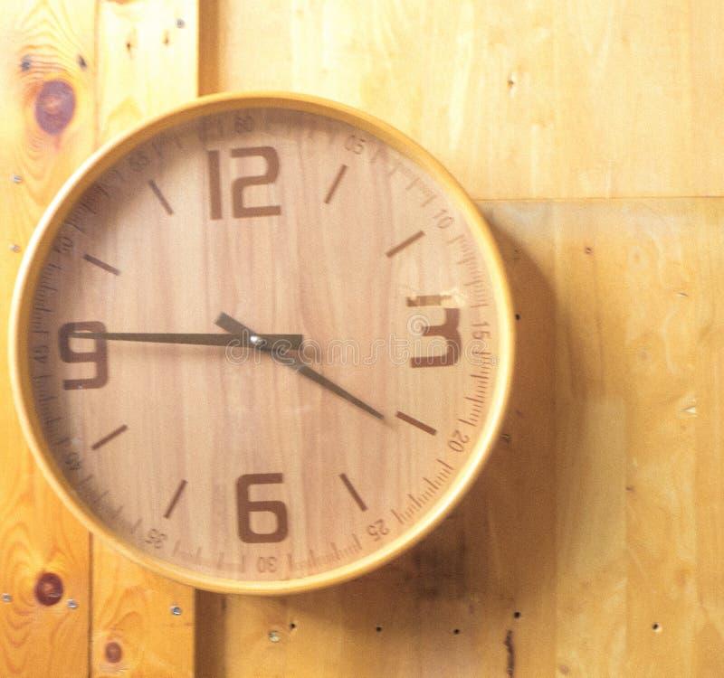 Orologio rotondo di legno della parete - orologio sul fondo di legno della natura di eco del fondo immagini stock libere da diritti