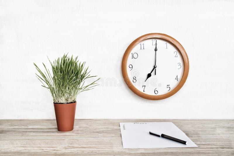 Orologio rotondo su una parete bianca, su una pianta da appartamento verde e su un foglio bianco di carta con una penna Pianifica fotografia stock libera da diritti