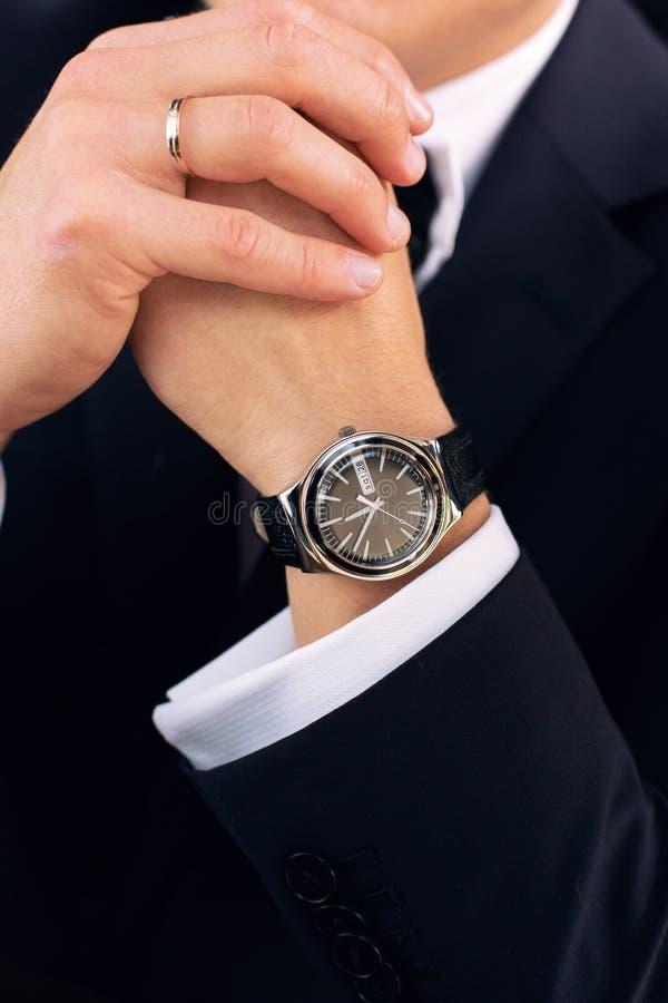 Orologio sulla mano dello sposo immagini stock