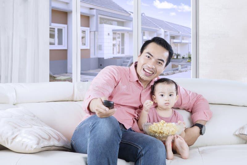 Orologio TV della bambina e del padre insieme fotografia stock