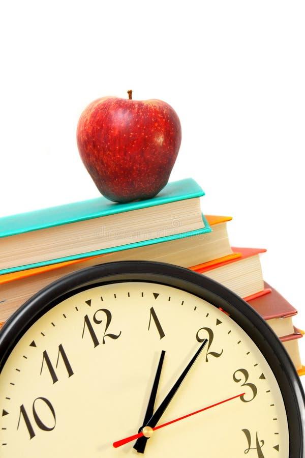 Orologio, una mela e libri fotografia stock