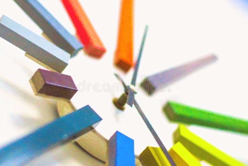 Orologio variopinto insolito moderno, meccanismo, estratto, tempo su struttura bianca del fondo fotografia stock