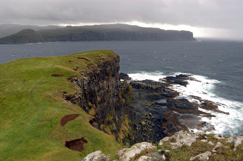 Oronsay with squally shower coming in. The cliffs on the island of Oronsay on the west coast of Skye royalty free stock image