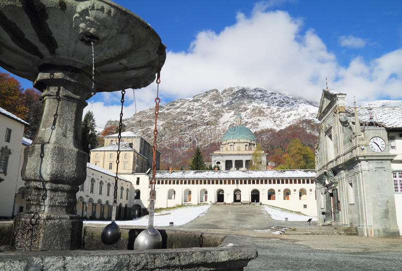 Oropa sanctuary fountain detail. And white mountain landscape in background stock images