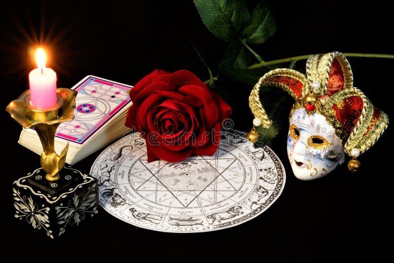 Oroscopo dello zodiaco, candela luminosa, rosa rossa, regina dei fiori, carte per le previsioni, maschera del giullare di carneva immagine stock libera da diritti