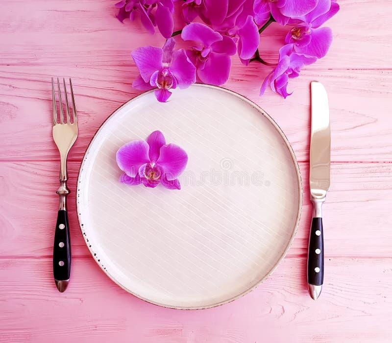 Orquídea de la flor, una placa en una cena de determinación de madera de la celebración de la decoración del fondo foto de archivo