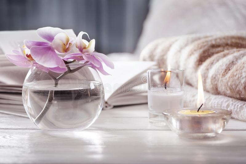 Orquídea em velas ardentes do ot seguinte do vaso na frente da cama Interior Home Ainda vida com detailes imagens de stock