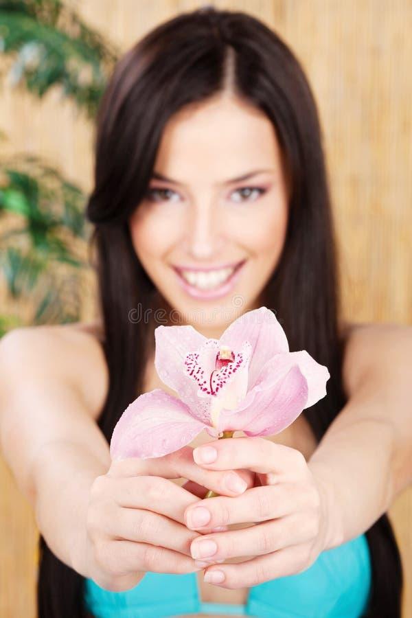Orquídea feliz da terra arrendada da mulher, foco na flor fotografia de stock