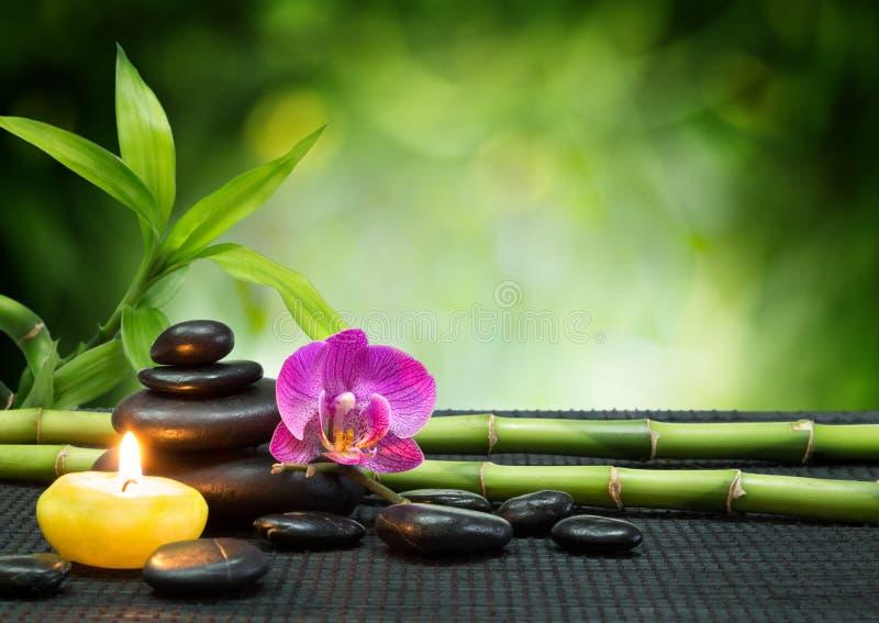 Orquídea púrpura, vela, con las piedras, bambú en la estera negra imagenes de archivo