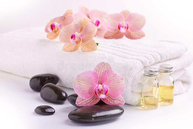 Orquídeas rosadas, aceites hidratantes y piedras del balneario en blanco imagen de archivo libre de regalías