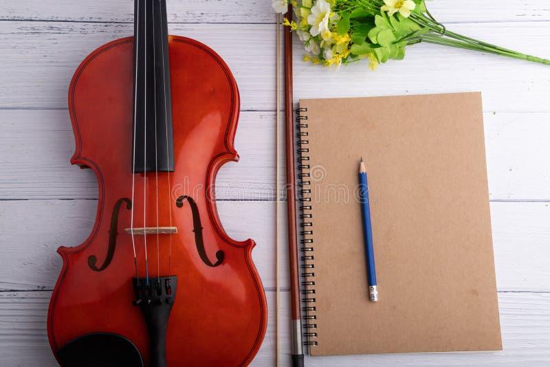 Orquesta del violín del tiro del primer instrumental y cuaderno sobre la profundidad baja del foco selecto de madera blanco del f fotos de archivo
