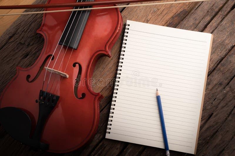 Orquesta del violín del tiro del primer instrumental y cuaderno sobre la profundidad baja del foco selecto de madera del fondo de imagenes de archivo