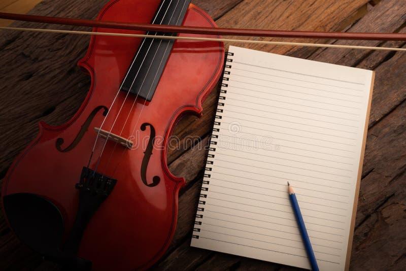 Orquesta del violín del tiro del primer instrumental y cuaderno sobre la profundidad baja del foco selecto de madera del fondo de imagen de archivo