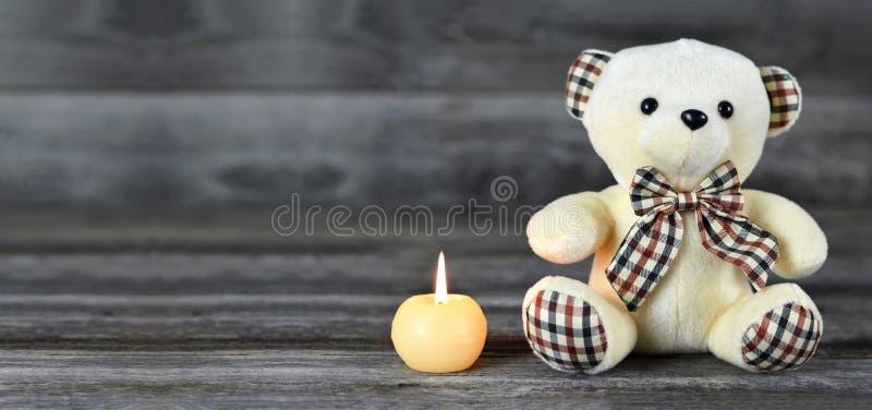Orsacchiotto e candela bianca su fondo di legno con lo spazio della copia fotografie stock