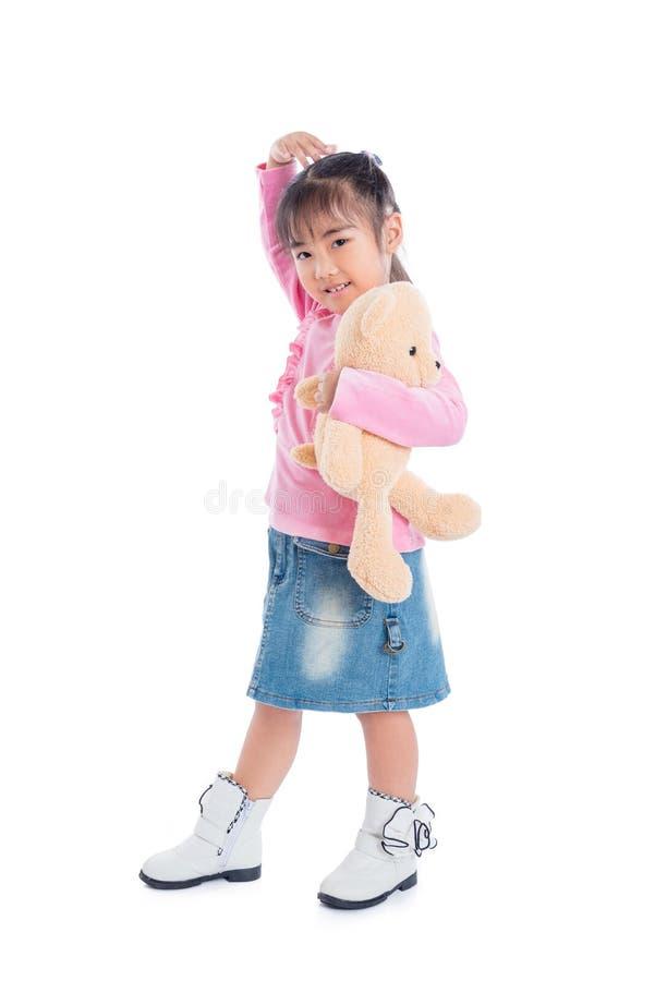 Orsacchiotto e sorrisi della tenuta della ragazza sopra bianco fotografia stock