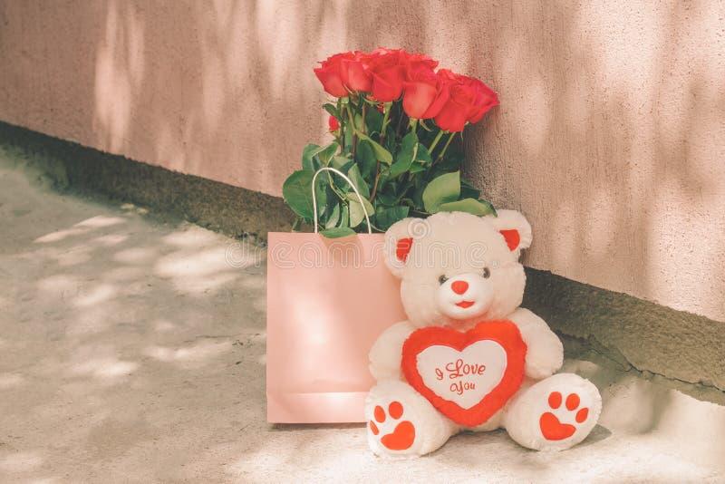 Orsacchiotto e un mazzo delle rose rosse in una borsa rosa fotografia stock libera da diritti