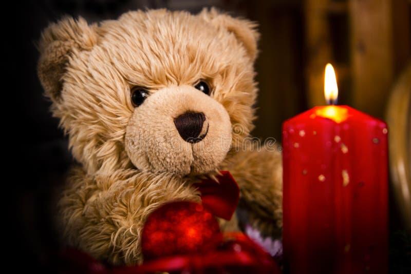Orsacchiotto e una candela bruciante rossa fotografia stock