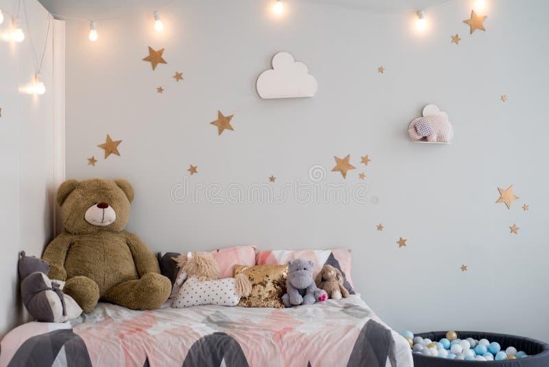 Orsacchiotto fra i sacchi di carta e le sedie di legno nella stanza del bambino con la lampada pastello sopra la tavola fotografie stock libere da diritti