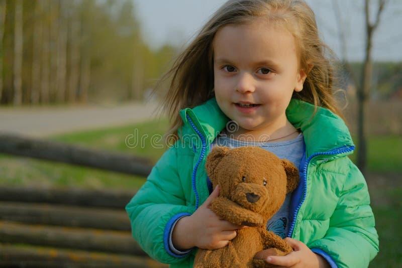 Orsacchiotto sorridente della tenuta della neonata all'aperto fotografia stock
