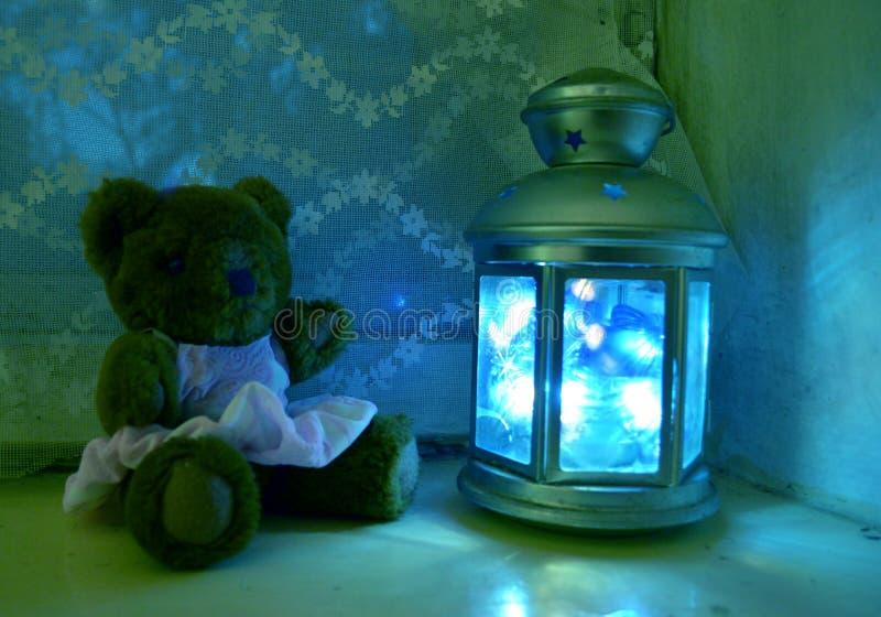 Orsacchiotto in un vestito sulla finestra uguagliante con una lampada magica immagine stock libera da diritti
