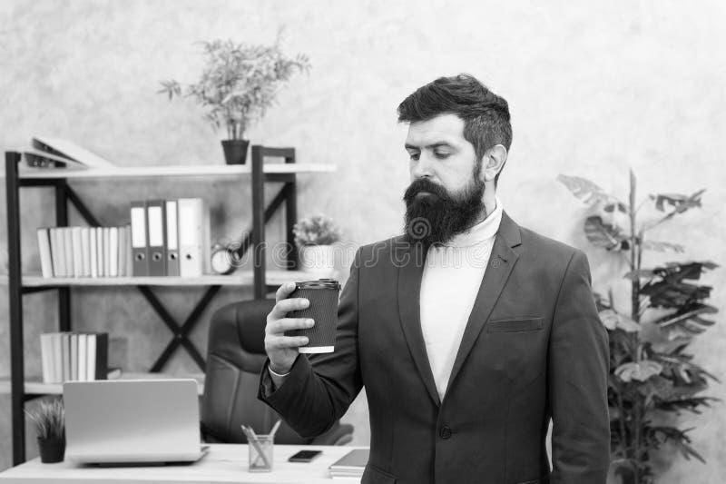Orsaker till att kaffet förbättrar kontorets kultur Affärsföretagare med skägg håller en kopp kaffe Avaxad chef royaltyfria bilder