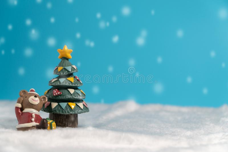 Orso bruno felice che porta il vestito da Santa con il contenitore di regali che colloca sulla neve vicino all'albero di Natale immagini stock