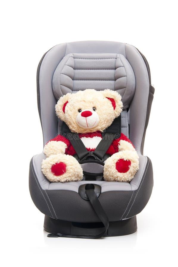 Orso dell'orsacchiotto che si siede sulla sede di automobile del bambino immagine stock