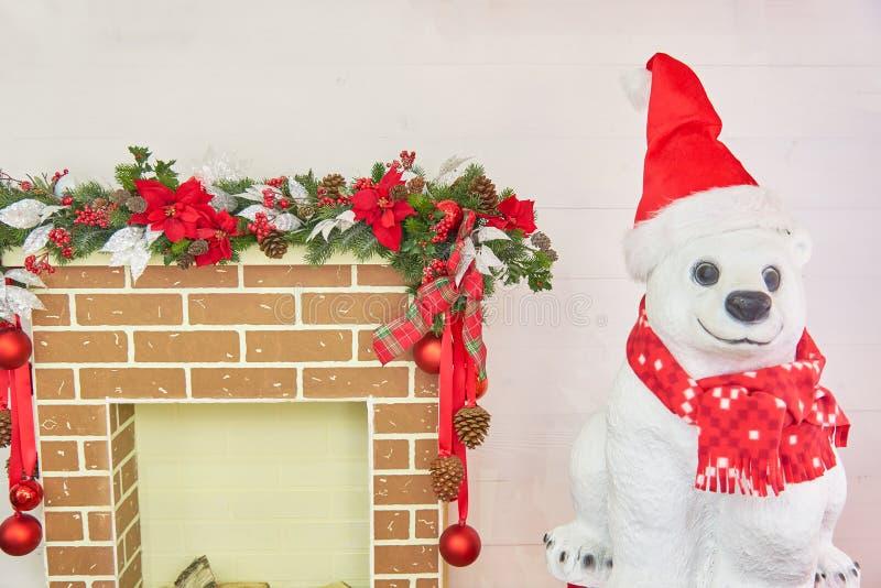 Orso polare con il camino di natale decorato con le palle e gli archi Interno della stanza di Natale immagini stock