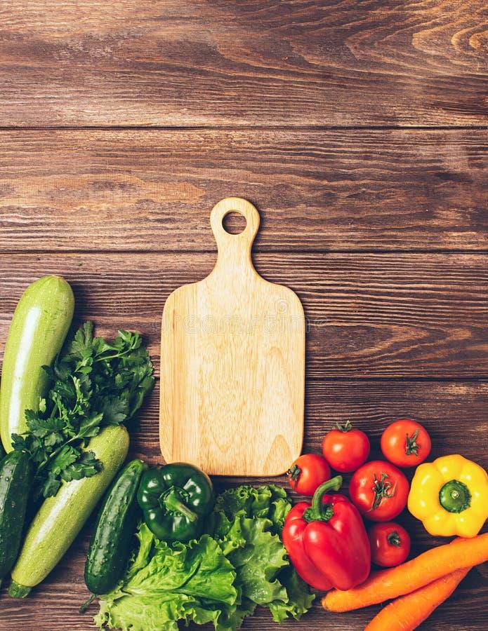 Ortaggi freschi del fondo di legno del tagliere differente di colori Vegetarianismo e nutrizione sana Disposizione piana fotografia stock