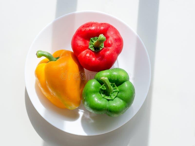 Ortaggi freschi del primo piano tre rossi dolci, giallo, peperoni verdi sul piatto fotografie stock libere da diritti