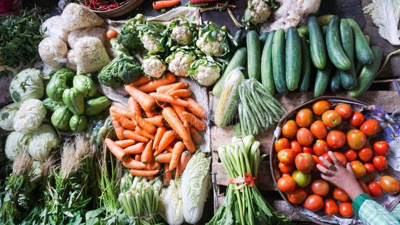 Ortaggi freschi sulla vendita nel mercato locale indonesiano - carote, cetrioli, cereale, pomodori, peperoncini rossi, verdi di s immagini stock libere da diritti