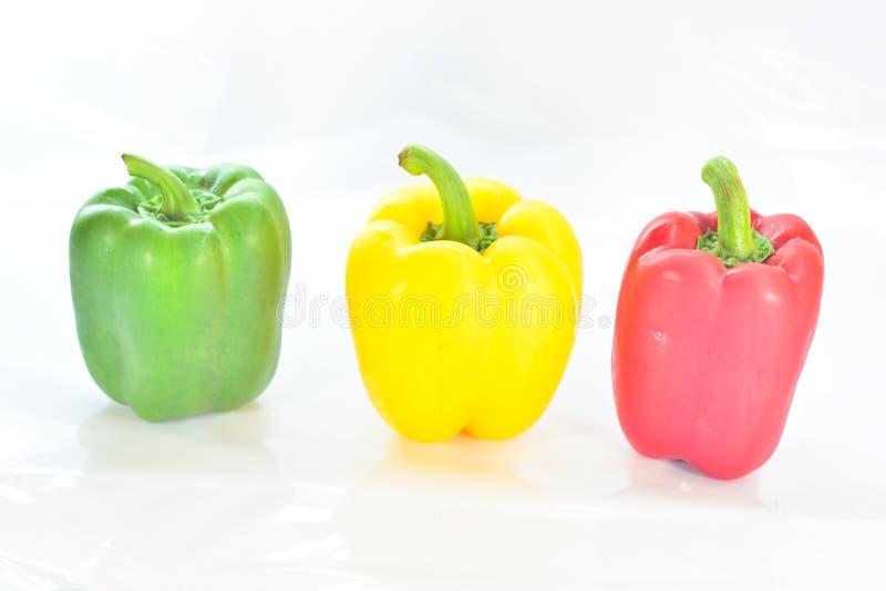 Ortaggi freschi tre rossi dolci, giallo, peperoni verdi isolati fotografia stock