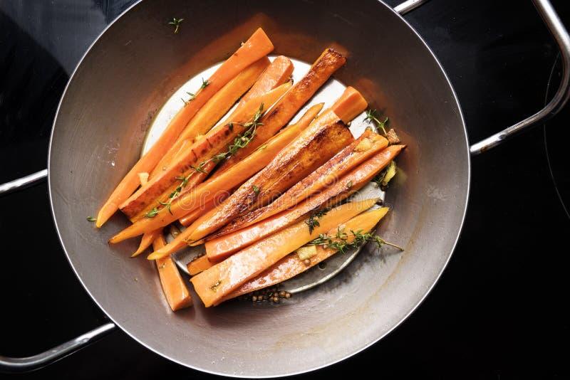 Ortaggi a radici, carote lustrate con timo, zenzero e miele dentro immagini stock