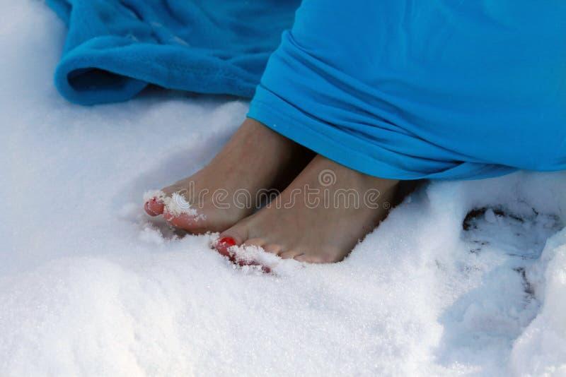 Orteils nus avec des ongles manucurés d'écarlate dans la neige image stock
