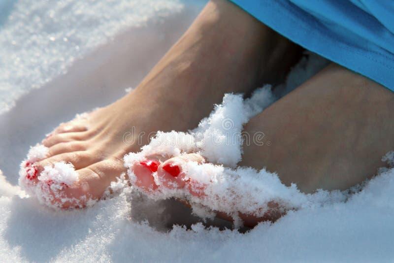 Orteils nus avec des ongles manucurés d'écarlate dans la neige photographie stock