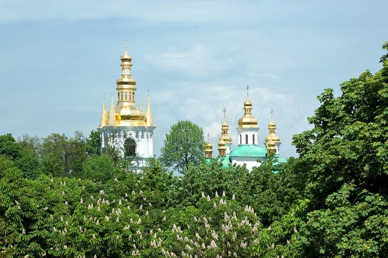 Orthodox churches peek out from behind the trees in Kyiv, Ukraine. Gilded domes of Christian Orthodox churches of Kyiv Pechersk Lavra peek out from behind the royalty free stock images