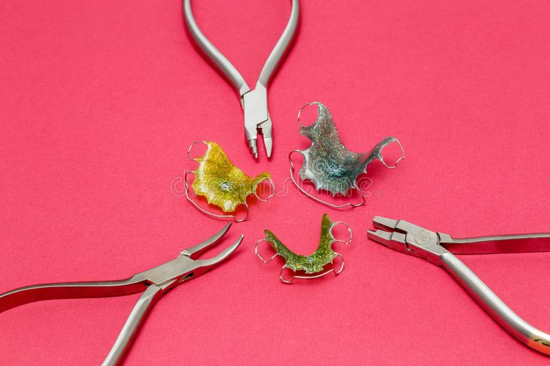 Orthodontic metal tools and dental braces or retainers, pink background stock images