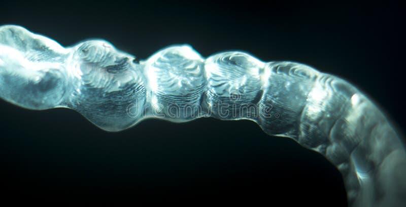 Orthodontics dental brace. Invisible orthodontics cosmetic brackets tooth aligners plastic braces modern teeth retainers isolated closeup stock photo
