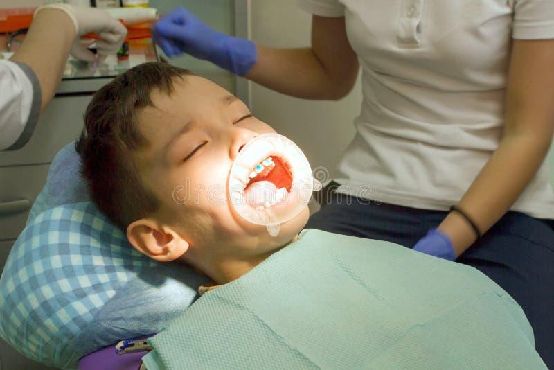 Orthodontist die jongensmond onderzoeken royalty-vrije stock afbeeldingen