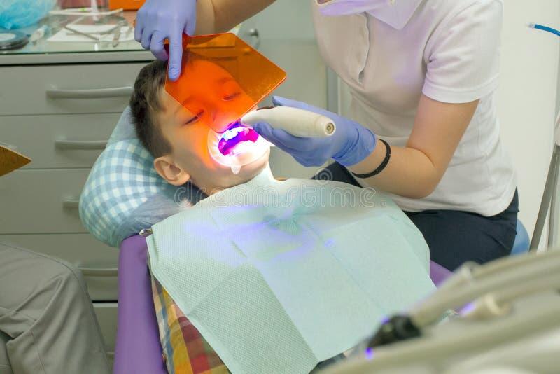 Orthodontist die jongensmond onderzoeken stock foto