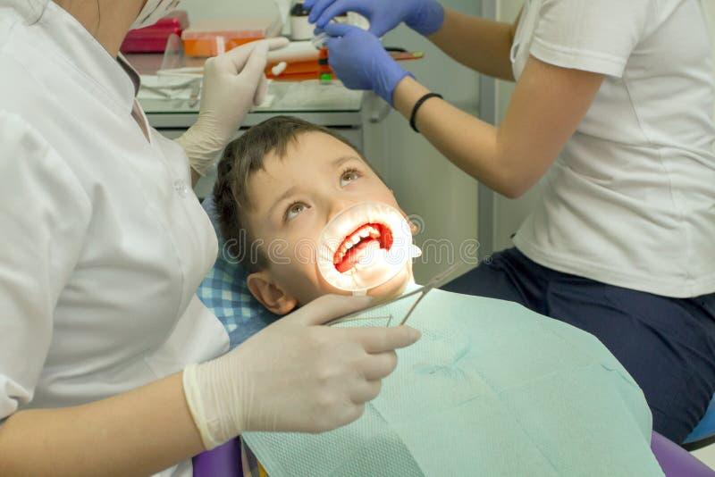 Orthodontist die jongensmond onderzoeken stock afbeelding