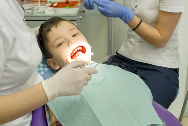 Orthodontist die jongensmond onderzoeken stock fotografie