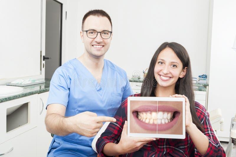 Orthodontist und Patient, die auf Tablette und dem Lächeln zeigen lizenzfreie stockbilder
