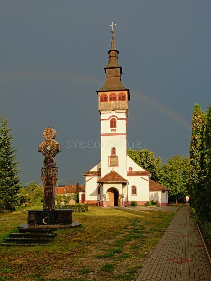 Orthodox assumption church in ORastie, Romania. Sunlit Assumption church of against a dark sky with rainbow in Orastie, Romania stock photography