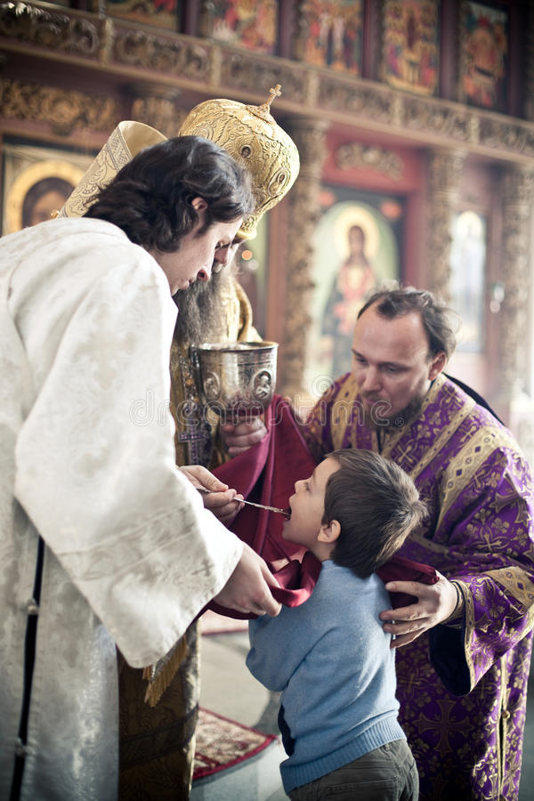 Orthodox bishop gives communion to a little boy